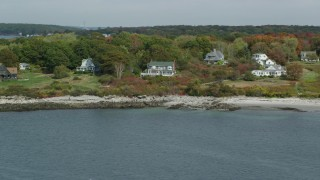 AX147_317 - 6k stock footage aerial video flying by oceanfront homes, Cushing Island, autumn, Portland, Maine