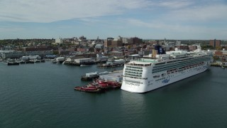 AX147_322 - 6k stock footage aerial video flying by docked cruise ship, piers and downtown, autumn, Portland, Maine