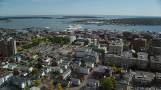 AX147_330 - 6k stock footage aerial video orbiting Portland Harbor, downtown buildings, autumn, Portland, Maine