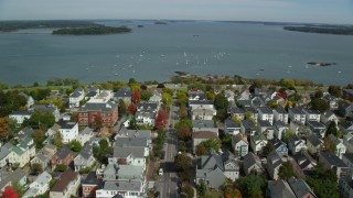 AX147_342 - 6k stock footage aerial video flying over coastal neighborhood to Eastern Promenade, bay,  Portland, Maine