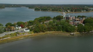 AX147_361 - 6k stock footage aerial video flying by waterfront homes, approach office buildups, small bridge, Portland, Maine