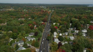AX147_364 - 6k stock footage aerial video flying over Route 1 through neighborhood, autumn, Falmouth, Maine