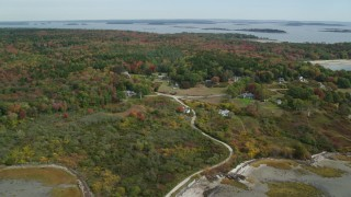 AX147_369 - 6k stock footage aerial video flying over rural homes, approaching small islands, autumn, Chebeague Island, Maine