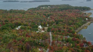 AX147_371 - 6k stock footage aerial video flying by rural homes on an island with colorful forest, Chebeague Island, Maine