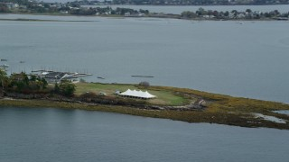 AX147_374 - 6k stock footage aerial video flying by a pavilion on an island, revealing a marina, autumn, Harpswell, Maine