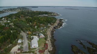 AX147_378 - 6k stock footage aerial video flying by coastal town, Bailey Island in autumn, Harpswell, Maine