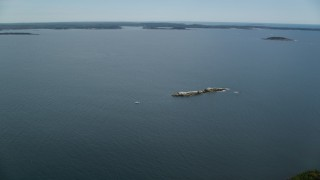 AX147_381 - 6k stock footage aerial video approaching, flying over Little Bull Ledge, fishing boat, bay, Harpswell, Maine