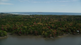 AX147_383 - 6k stock footage aerial video flying over a colorful forest, revealing rural homes, Phippsburg, Maine