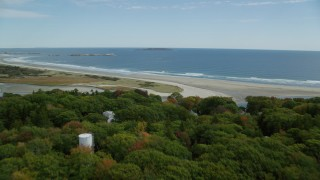 AX147_384 - 6k stock footage aerial video flying over rural homes, colorful forest, approaching the beach, Phippsburg, Maine