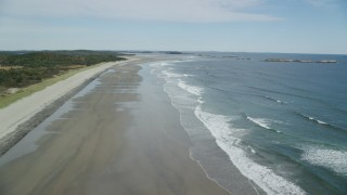 AX147_385 - 6k stock footage aerial video flying by waves rolling onto the beach, autumn, Phippsburg, Maine