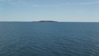 AX147_386 - 6k stock footage aerial video flying low over the ocean approaching boat and Seguin Island, Phippsburg, Maine