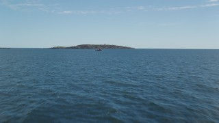 AX147_387 - 6k stock footage aerial video flying low over ocean, approaching a boat and Seguin Island, Phippsburg, Maine