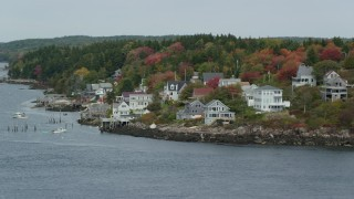 AX147_397 - 6k stock footage aerial video flying by waterfront homes, colorful trees, autumn, Georgetown, Maine