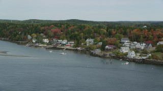 AX147_398 - 6k stock footage aerial video flying over waterfront homes, colorful trees in autumn, Georgetown, Maine