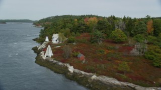AX147_401 - 6k stock footage aerial video flying by Perkins Island Light, Perkins Island, autumn, Georgetown, Maine