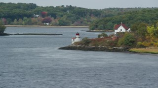 AX147_402 - 6k stock footage aerial video flying by Squirrel Point Light, autumn foliage, Arrowsic, Maine
