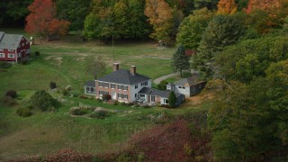 AX147_407 - 6k stock footage aerial video flying by an isolated waterfront home, colorful autumn trees, Phippsburg, Maine