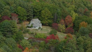 AX147_409 - 6k stock footage aerial video flying by an isolated rural home, colorful trees in autumn, Arrowsic, Maine
