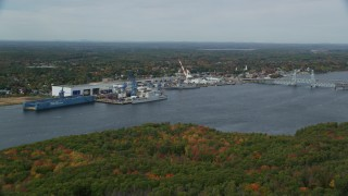 AX147_411 - 6k stock footage aerial video flying by waterfront General Dynamics Bath Iron Works, autumn, Bath, Maine