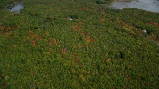 AX147_416 - 6k stock footage aerial video of a bird's eye view over colorful forest, rural homes, autumn, Woolwich, Maine
