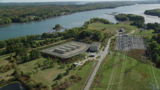 AX148_001 - 6k stock footage aerial video flying by an electrical substation near a river, autumn, Wiscasset, Maine