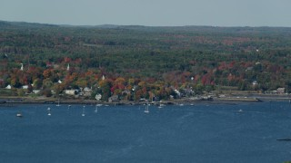 AX148_002 - 6k stock footage aerial video flying by a small waterfront town, autumn, Wiscasset, Maine