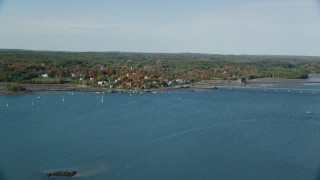 AX148_004 - 6k aerial stock footage video approaching small waterfront town, autumn, Wiscasset, Maine