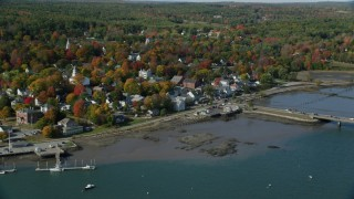 AX148_005 - 6k stock footage aerial video approaching small waterfront town, tilt down, Main Street, autumn, Wiscasset, Maine