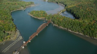 AX148_006 - 6k stock footage aerial video flying by a small bridge spanning Sheepscot River, autumn, Newcastle, Maine
