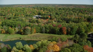 AX148_008 - 6k stock footage aerial video flying over colorful forest, approach small warehouse, autumn, Newcastle, Maine