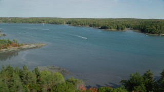 AX148_015 - 6k stock footage aerial video flying by sport boat on the Damariscotta River, autumn, Newcastle, Maine