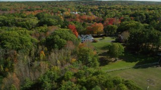 AX148_017 - 6k stock footage aerial video approaching an isolated home, colorful forest, autumn, Damariscotta, Maine
