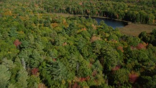 AX148_019 - 6k stock footage aerial video flying over a colorful forest and Lower Pond, autumn, Damariscotta, Maine