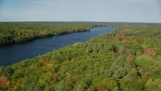 AX148_023 - 6k stock footage aerial video flying by a colorful forest, Biscay Pond, autumn, Damariscotta, Maine