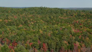 AX148_026 - 6k stock footage aerial video flying over a colorful forest, approaching a watchtower, autumn, Bremen, Maine