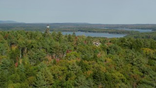 AX148_027 - 6k stock footage aerial video flying over colorful forest, by watchtower, approach Broad Cove, Bremen, Maine