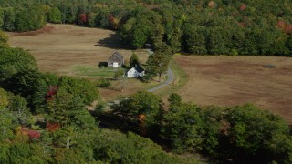 AX148_028 - 6k stock footage aerial video flying over colorful forest, approach small farm, barn, autumn, Bremen, Maine