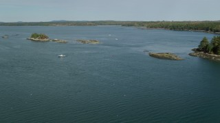 AX148_031 - 6k stock footage aerial video flying by tiny islands, fishing boats, The Narrows. autumn, Waldoboro, Maine