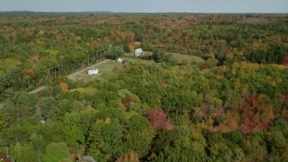 AX148_033 - 6k stock footage aerial video flying over rural homes and colorful forest in autumn, Waldoboro, Maine