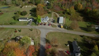 AX148_035 - 6k stock footage aerial video flying over rural road by homes in a colorful forest, autumn, Waldoboro, Maine