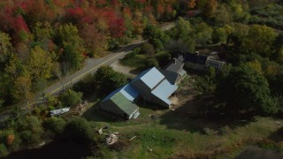AX148_038 - 6k stock footage aerial video flying over colorful forest, approach rural home, small ponds, autumn, Cushing, Maine