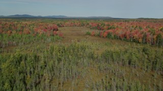 AX148_040 - 6k stock footage aerial video flying over a colorful forest, small river, autumn, Cushing, Maine