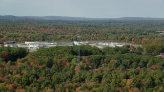 AX148_061 - 6k stock footage aerial video flying by Maine State Prison, colorful forest, autumn, Warren, Maine