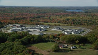 AX148_063 - 6k stock footage aerial video orbiting Maine State Prison, colorful forest, autumn, Warren, Maine