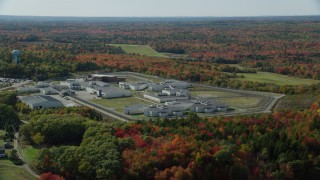 AX148_064 - 6k stock footage aerial video orbiting Maine State Prison, colorful forest, autumn, Warren, Maine