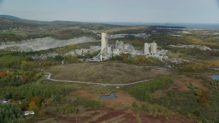 AX148_073 - 6k stock footage aerial video flying by quarry and factory, autumn, Thomaston, Maine
