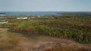 AX148_075 - 6k stock footage aerial video flying by colorful forest, approach warehouse buildings, autumn, Rockland, Maine