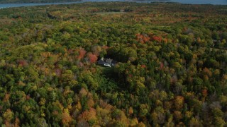 AX148_079 - 6k stock footage aerial video flying by a lone rural home, colorful forest, autumn, Owls Head, Maine