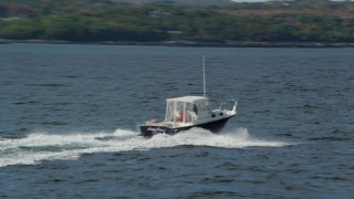 AX148_089 - 6k stock footage aerial video tracking a speeding boat on the water, Owls Head, Maine