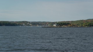 AX148_090 - 6k stock footage aerial video flying low over water, approaching Indian Island Light, autumn, Rockport, Maine
